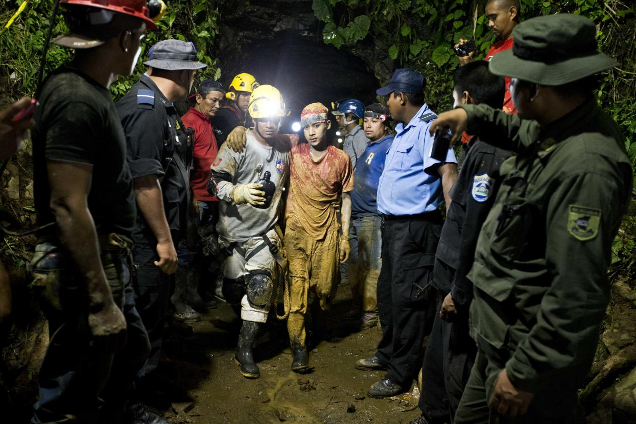 Leber Vivas Gonzales, 16, center right, is accompanied by a rescue worker as he walks away from the entrance to the El Comal gold and silver mine in Bonanza, Nicaragua, Friday, Aug. 29, 2014. Vivas was the first of 11 freelance gold miners trapped by a collapse in the mine to be rescued and crews were working early Saturday to free more the rest, officials said. (AP Photo/Esteban Felix)