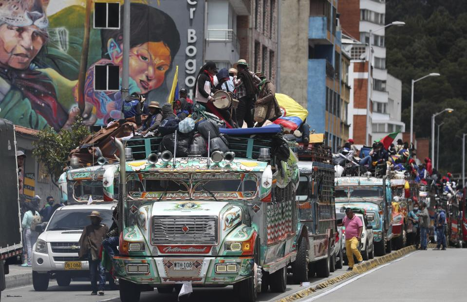 Members of the Indigenous Guard arrive in a caravan of buses to take part in a national strike in Bogota, Colombia, Wednesday, Oct. 21, 2020. Workers' unions, university students, human rights defenders, and Indigenous communities have gathered for a day of protest in conjunction with a national strike across Colombia. The protest is against the assassinations of social leaders, in defense of the right to protest and to demand advances in health, income and employment. (AP Photo/Fernando Vergara)