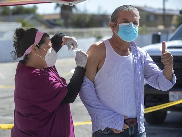 PACOIMA, CA - MARCH 4, 2021: Ponciano Sánchez, 57, of Pacoima, raises his thumb while receiving a vaccination from RN Celeste Montoya at a COVID-19 vaccination pop-up site located at the Seventh-day Adventist Church from Valley Crossroads in Pacoima.  Pop-up vaccination sites will be offered to residents of Los Angeles City Councilmember Mónica Rodríguez's district in the northeast San Fernando Valley for the next three weeks.  (Mel Melcon / Los Angeles Times)