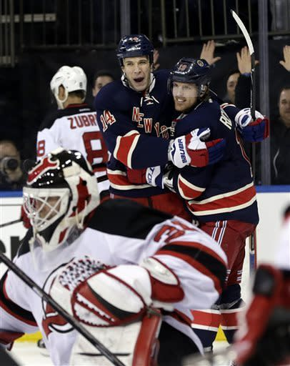 New York Rangers' Taylor Pyatt (14), top center, celebrates his goal with teammate Brad Richards during the second period of an NHL hockey game against the New Jersey Devils, Sunday, April 21, 2013, in New York. (AP Photo/Seth Wenig)