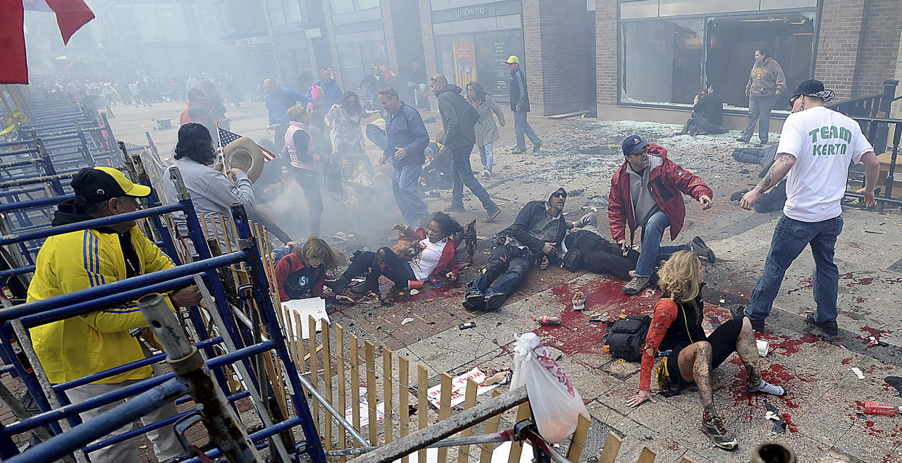 Injured people and debris lie on the sidewalk near the Boston Marathon finish line following an explosion in Boston, Monday, April 15, 2013. (AP Photo/MetroWest Daily News, Ken McGagh) MANDATORY CREDIT