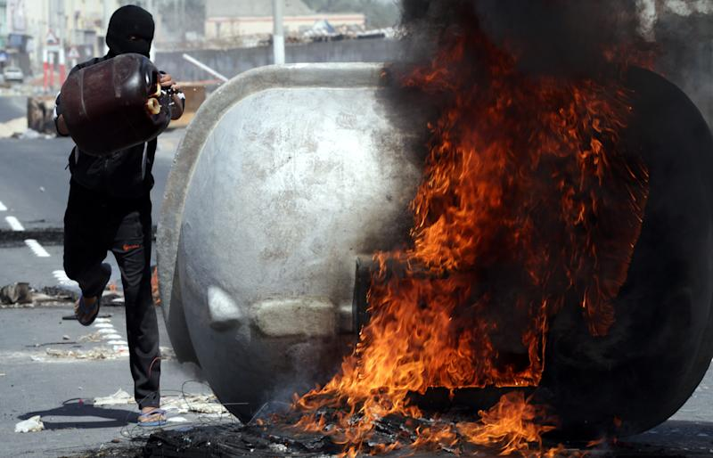 """A Bahraini anti-government protester adds fuel to a burning water tank in Malkiya village, Bahrain, Thursday, March 14, 2013. Protests and clashes erupted in opposition areas nationwide Thursday with government opponents observing a """"Dignity Strike"""" blocking roads, closing shops, protesting and staying home from work and school, called by the more radical February 14 youth group. (AP Photo/Hasan Jamali)"""