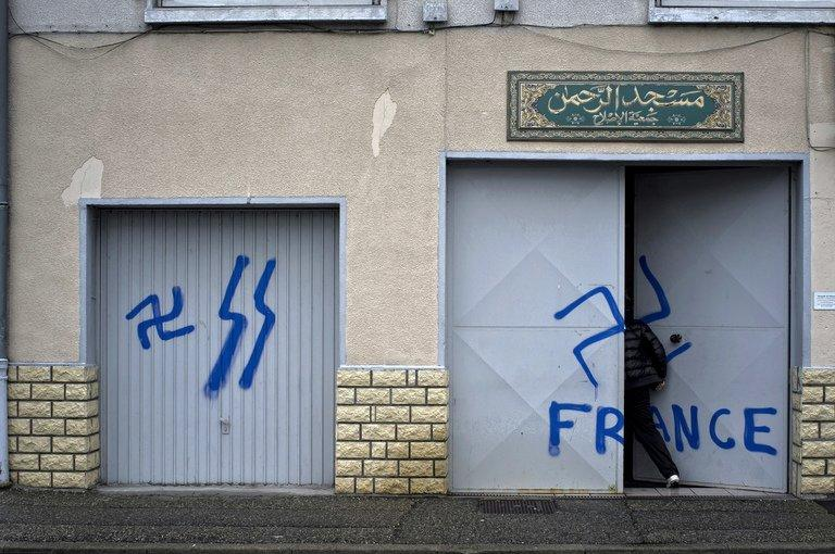 A worshiper opens the door of a mosque where nazi graffiti had been sprayed, on December 20, 2011 in Décines, Lyon