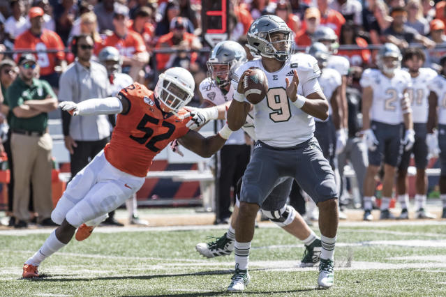 Eastern Michigan quarterback Mike Glass, III (9) is pressured by Illinois defensive end Ayo Shogbonyo (52) in the first half of a NCAA college football game between Illinois and Eastern Michigan, Saturday, Sept.14, 2019, in Champaign, Ill. (AP Photo/Holly Hart)
