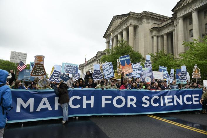 people with signs at a March for Science in DC