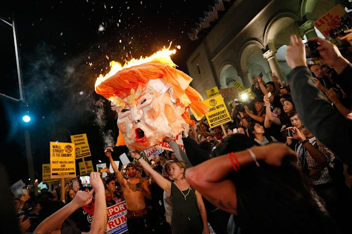 <p>Protesters burn an effigy of Donald Trump outside Los Angeles City Hall in Calif., on Nov.9, 2016. (Photo: Marcus Yam/Los Angeles Times via Getty Images) </p>