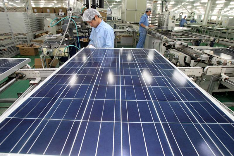 FILE - In this Nov. 18, 2011 file photo released by China's Xinhua News Agency, Chinese work on the production line at a solar panel factory of the Eoplly New Energy Technology Co., Ltd. in Nantong City, east China's Jiangsu Province. The Obama administration moved Thursday, May 17, 2012 to impose stiff new tariffs on solar panels made in China, finding that Chinese companies are improperly flooding the U.S. market with government-subsidized products. (AP Photo/Xinhua, Xu Congjun, File) NO SALES