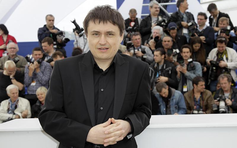 Director Director Christian Mungiu, center, smiles during a photo call for Beyond the Hills at the 65th international film festival, in Cannes, southern France, Saturday, May 19, 2012. (AP Photo/Francois Mori)