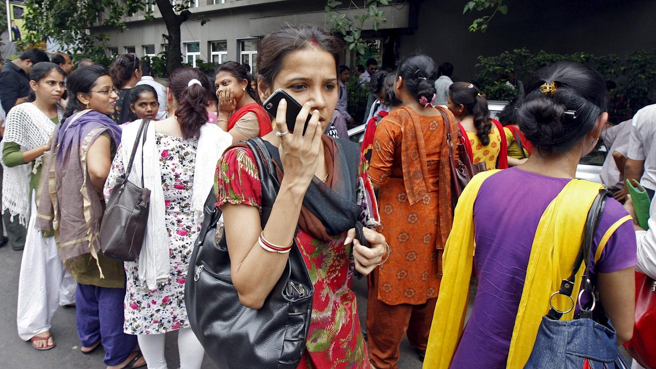A woman speaks on her mobile phone as she stands with others after vacating their office buildings following an earthquake in Kolkata