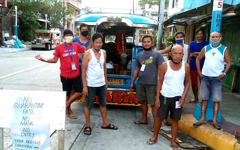 Jowel Palana (centre, blue t-shirt), in Manila with his vehicle - a 'jeepney' - Dan Olanday