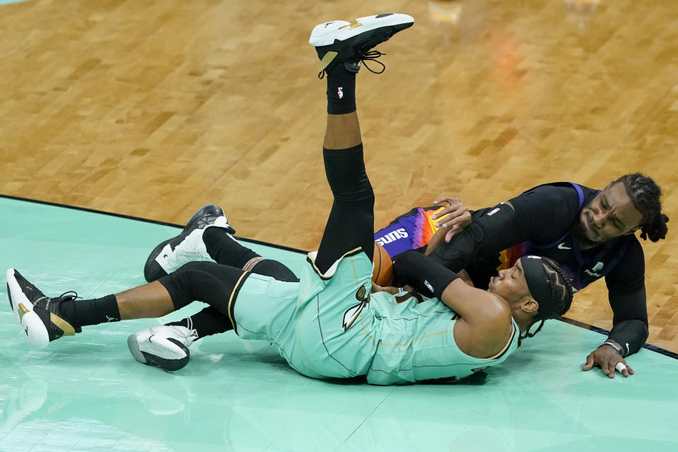 Charlotte Hornets guard Devonte' Graham and Phoenix Suns forward Jae Crowder battle for a loose ball during the second half of an NBA basketball game on Sunday, March 28, 2021, in Charlotte, N.C. (AP Photo/Chris Carlson)