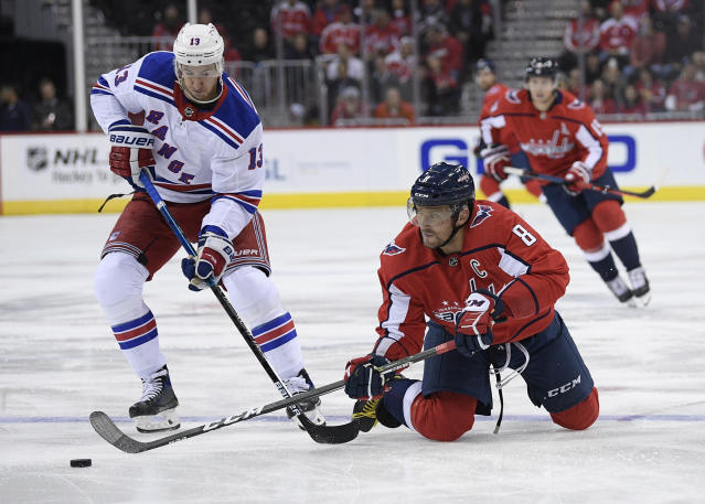 Washington Capitals left wing Alex Ovechkin (8), of Russia, battles for the puck against New York Rangers center Kevin Hayes (13) during the first period of an NHL hockey game, Wednesday, Oct. 17, 2018, in Washington. (AP Photo/Nick Wass)