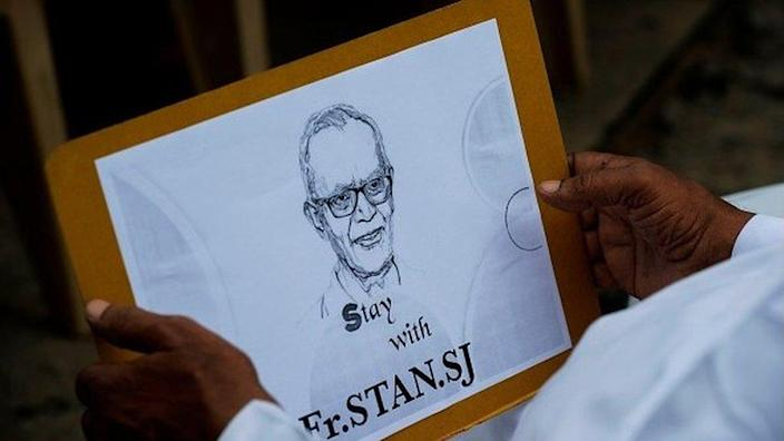 A Catholic priest holds a placard with the image of Jesuit priest Father Stan Swamy during a protest against his arrest in the eastern Indian state of Jharkhand .