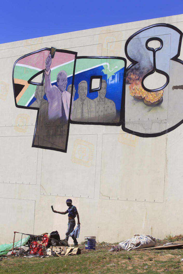 A homeless man walks past a mural depicting former South African President Nelson Mandela, top left, in the city of Cape Town, South Africa, Sunday, March 10, 2013. South Africa's presidency says Nelson Mandela has spent a night in the hospital after he was admitted for tests. Presidential spokesman Mac Maharaj said Sunday there were no updates on 94-year-old Mandela's condition since he went to a hospital in Pretoria on Saturday afternoon. The full graffiti mural is numbers depicting history in the decades 90's 80's 70's. (AP Photo/Schalk van Zuydam)