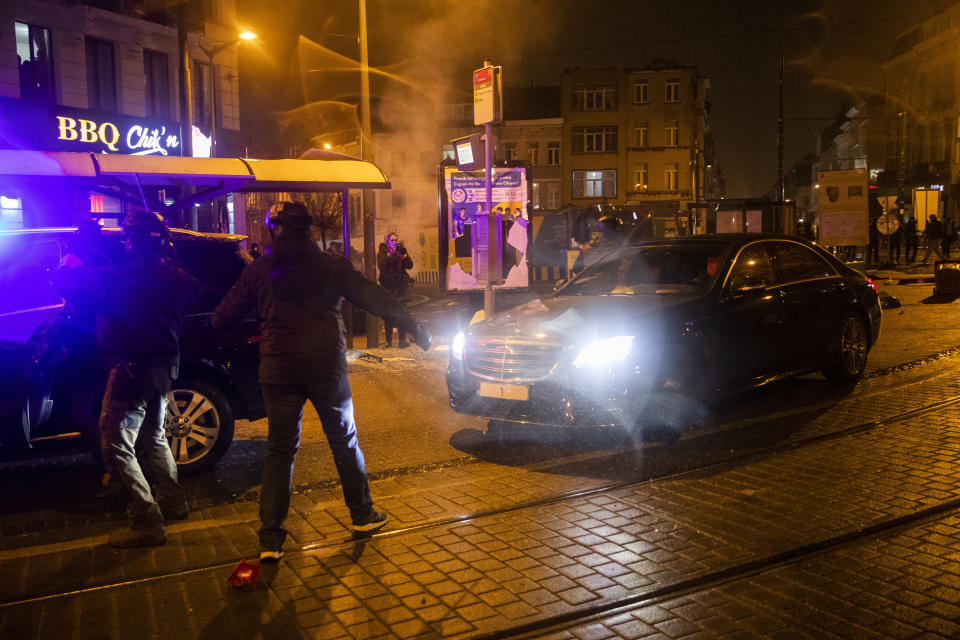 The escorted official car of Belgium's King Philippe makes a turn to avoid protestors in the Belgium capital, Brussels, Wednesday, Jan. 13, 2021, at the end of a protest asking for authorities to shed light on the circumstances surrounding the death of a 23-year-old Black man who was detained by police last week in Brussels. The demonstration in downtown Brussels was largely peaceful but was marred by incidents sparked by rioters who threw projectiles at police forces and set fires before it was dispersed. (AP Photo/Francisco Seco)
