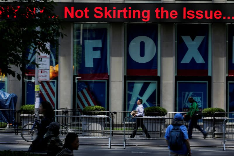 FILE PHOTO: People pass by ads of Fox News channel at the News Corporation building in the Manhattan borough of New York City, New York