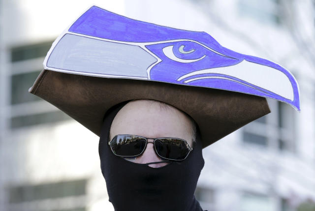 A Seattle Seahawks fan waits in the cold for the start of the Super Bowl champions parade to begin Wednesday, Feb. 5, 2014, in Seattle. The Seahawks beat the Denver Broncos 43-8 in NFL football's Super Bowl XLVIII on Sunday. (AP Photo/John Froschauer)