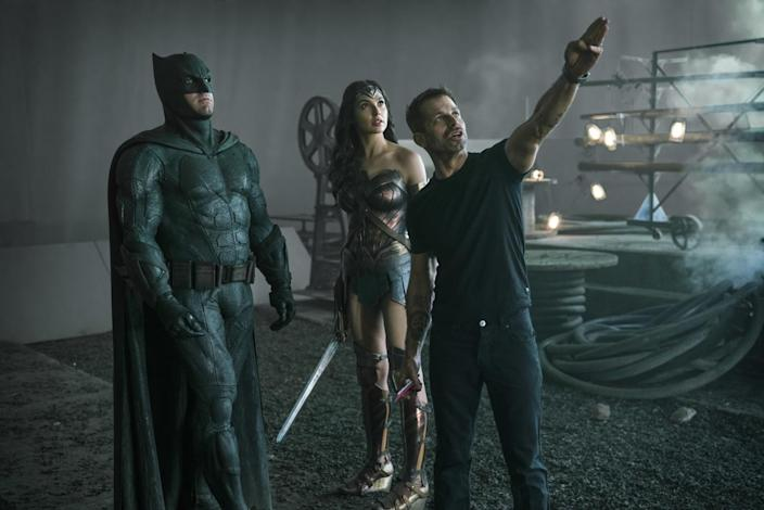 Ben Affleck as Batman standing with Gal Gadot as Wonder Woman while Zack Snyder directs