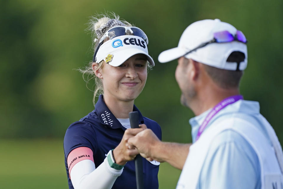 Nelly Korda, left, fist-bumps her caddie after a birdie on the ninth hole during the second round of play in the KPMG Women's PGA Championship golf tournament Friday, June 25, 2021, in Johns Creek, Ga. (AP Photo/John Bazemore)