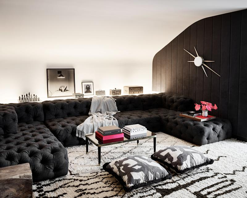 """Fabric walls in the media room create a warm, inviting atmosphere for family gatherings and McFayden's son's teenage hangouts. """"The big sliding doors here and elsewhere downstairs are a way to create privacy while also creating spaciousness,"""" says Lamb. """"Being dug into the ground, the room really needed the light."""" The sofa is by RH."""