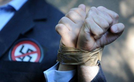 Activists from the European Union of Jewish Students stand with their hands taped to each other's in front of Laszlo Csatary's hideaway building in Hungary. Hungarian authorities detained, grilled and put under house arrest on Wednesday 97-year-old Csatary