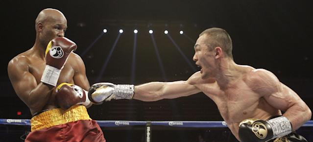 Beibut Shumenov right, of Kazakhstan, punches Bernard Hopkins, of the United States, during the third round of their IBF, WBA and IBA Light Heavyweight World Championship unification boxing match, Saturday, April 19, 2014, in Washington. Hopkins won by a split decision. (AP Photo/Luis M. Alvarez)