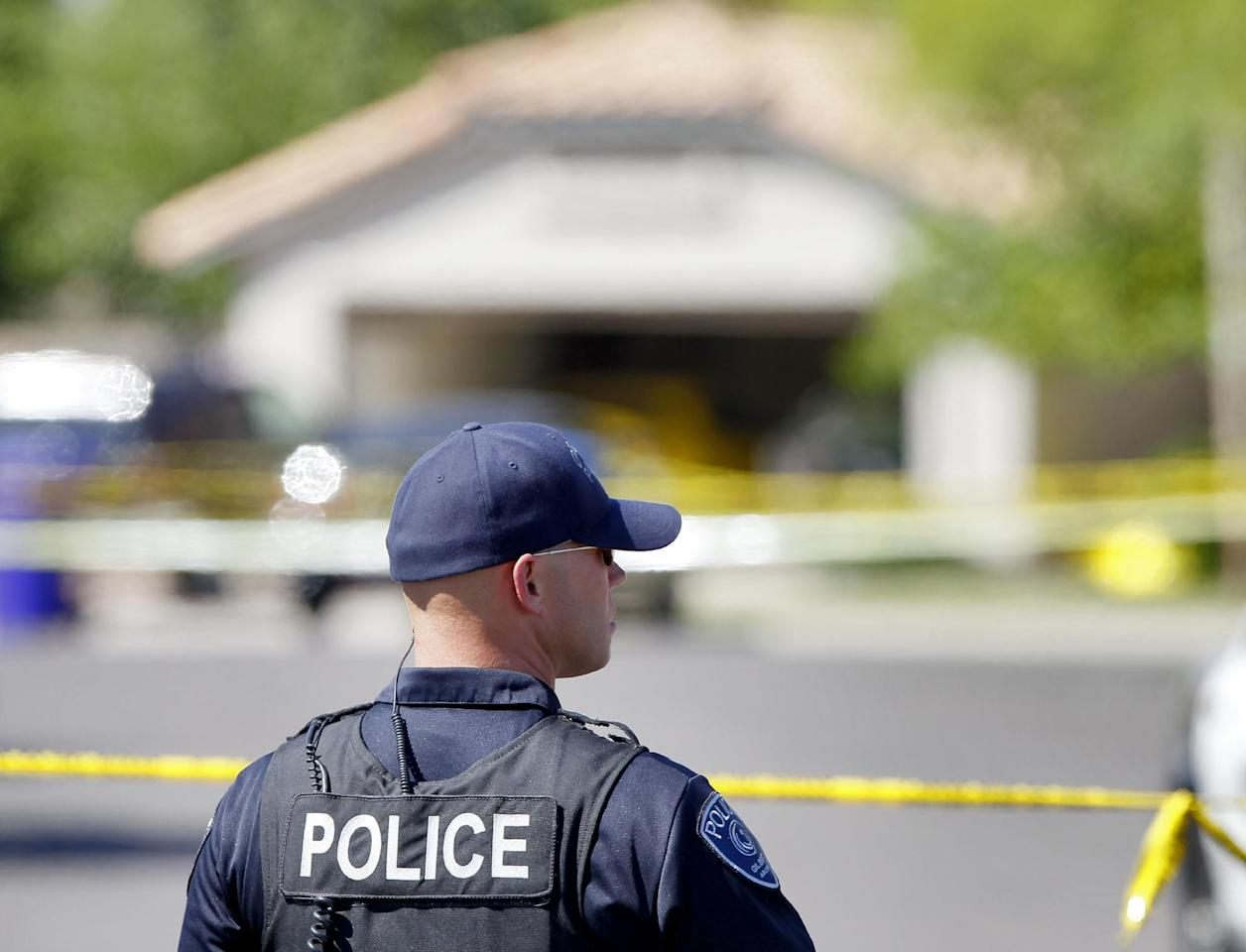 A Gilbert police officer stands outside the police tape outside a crime scene Wednesday, May 2, 2012 in Gilbert, Ariz. Police in the Phoenix suburb of Gilbert say a man shot and killed four people, including a toddler, before killing himself. (AP Photo/Matt York)