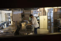 Chef Kayes Ghourabi works in the kitchen as he prepares take-away meals in his restaurant, Tartufo, in Sint-Pieters-Leeuw, Belgium, Thursday, Oct. 22, 2020. The coronavirus pandemic is gathering strength again in Europe and, with winter coming, its restaurant industry is struggling. The spring lockdowns were already devastating for many, and now a new set restrictions is dealing a second blow. Some governments have ordered restaurants closed; others have imposed restrictions curtailing how they operate. (AP Photo/Francisco Seco)