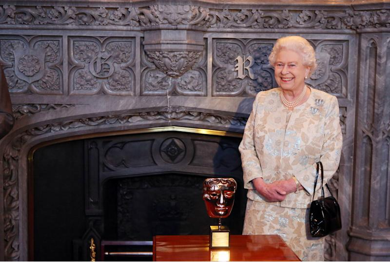 "Queen Elizabeth II receives an honorary British Academy award (Bafta) Thursday April 4 2013, at Windsor Castle, west of London, from actor and director Kenneth Branagh, unseen, in recognition of her lifetime's support of British film and television - and for being the most ""memorable Bond girl yet"", in her London Olympics opening role. (AP Photo/Steve Parsons, pool)"