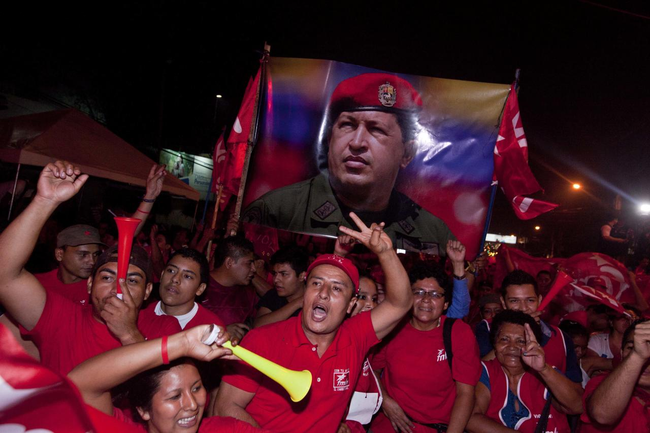 Supporters of presidential candidate Salvador Sanchez Ceren, of the ruling Farabundo Marti National Liberation Front (FMLN), hold up an image of Venezuela's late President Hugo Chavez as they celebrate after partial results were announced by election authorities in San Salvador, El Salvador, Sunday, March 9, 2014. El Salvador's too-close-to-call presidential runoff election has raised competing claims of victory from Ceren, a former fighter for leftist guerrillas and the candidate of the once long-ruling conservative party that fought a civil war from 1980 to 1992. (AP Photo/Esteban Felix)