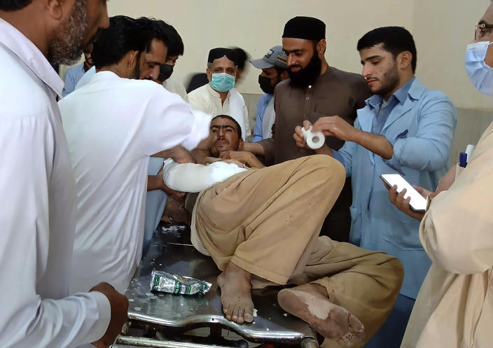 A man injured in a bus accident is treated at a hospital in Khuzdar, a remote district in the Pakistan's southwestern Baluchistan province, Friday, June 11, 2021. A speeding bus carrying pilgrims overturned on a highway and fell into a ravine in a remote area in southwestern Pakistan before dawn on Friday, killing more than a dozen and injuring scores of people, police and officials said. (AP Photo/Younis Baloch)