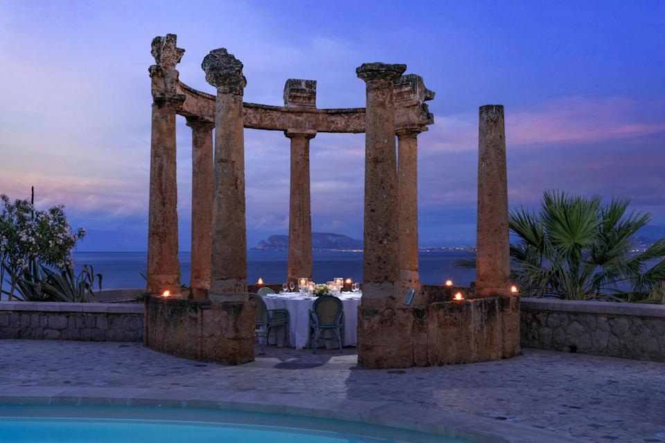 A private dining area at dusk in the gardens of Villa Igiea.