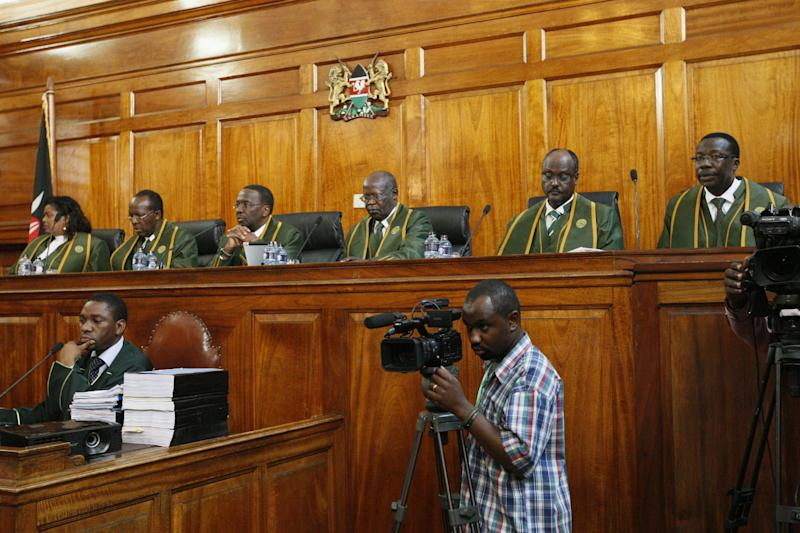 Six Supreme Court judges, led by Chief Justice Willy Mutunga, seated third left, listen to a petition from Kenya's Prime Minister Raila Odinga filed against president-elect Uhuru Kenyatta at the Supreme Courts in Nairobi, Kenya, Monday, March 25, 2013. The court ordered the election commission to recount votes in 22 of the country's 291 constituencies to see if any of the tallies exceed the number of registered voters, after Uhuru Kenyatta was named the winner of the March 4 Presidential election with 50.07 per cent of the vote.(AP Photo/Sayyid Azim)