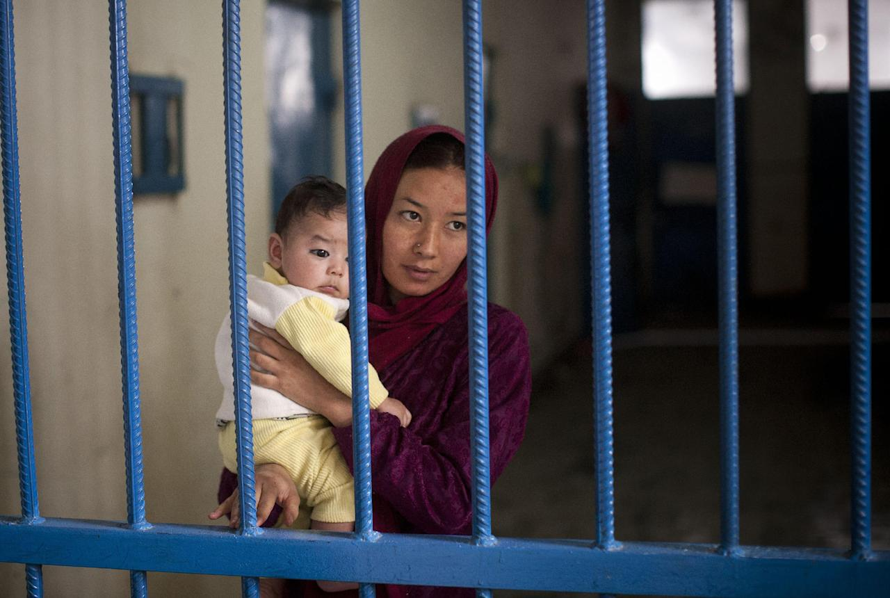"""Picture taken March 28, 2013 shows Afghan female prisoner Nuria with her infant boy at Badam Bagh, Afghanistan's central women's prison, in Kabul, Afghanistan. """"When I went to court for the divorce, instead of giving me a divorce, they charged me with running away,"""" Nuria said. The man she wanted to marry was also charged and is now serving time in Afghanistan's notorious Pul-e-Charkhi prison. 202 women living in the six- year- old jail, the majority of the women are serving sentences of up to seven years for leaving their husbands, refusing to accept a marriage arranged by their parents, or choosing to leave their parent's home with a man of their choice. (AP Photo/Anja Niedringhaus)"""