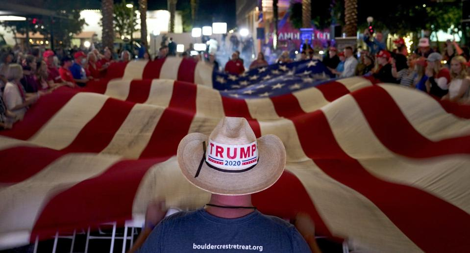 """<span class=""""caption"""">President Donald Trump supporters wave a flag during an election watch party Nov. 3, 2020, in Chandler, Ariz. </span> <span class=""""attribution""""><span class=""""source"""">(AP Photo/Matt York)</span></span>"""