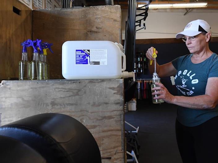 Co-owner Monica Cole fills spray bottles with disinfectant as she gets ready to open for business at CrossFit Apollo, which has been closed since March 17
