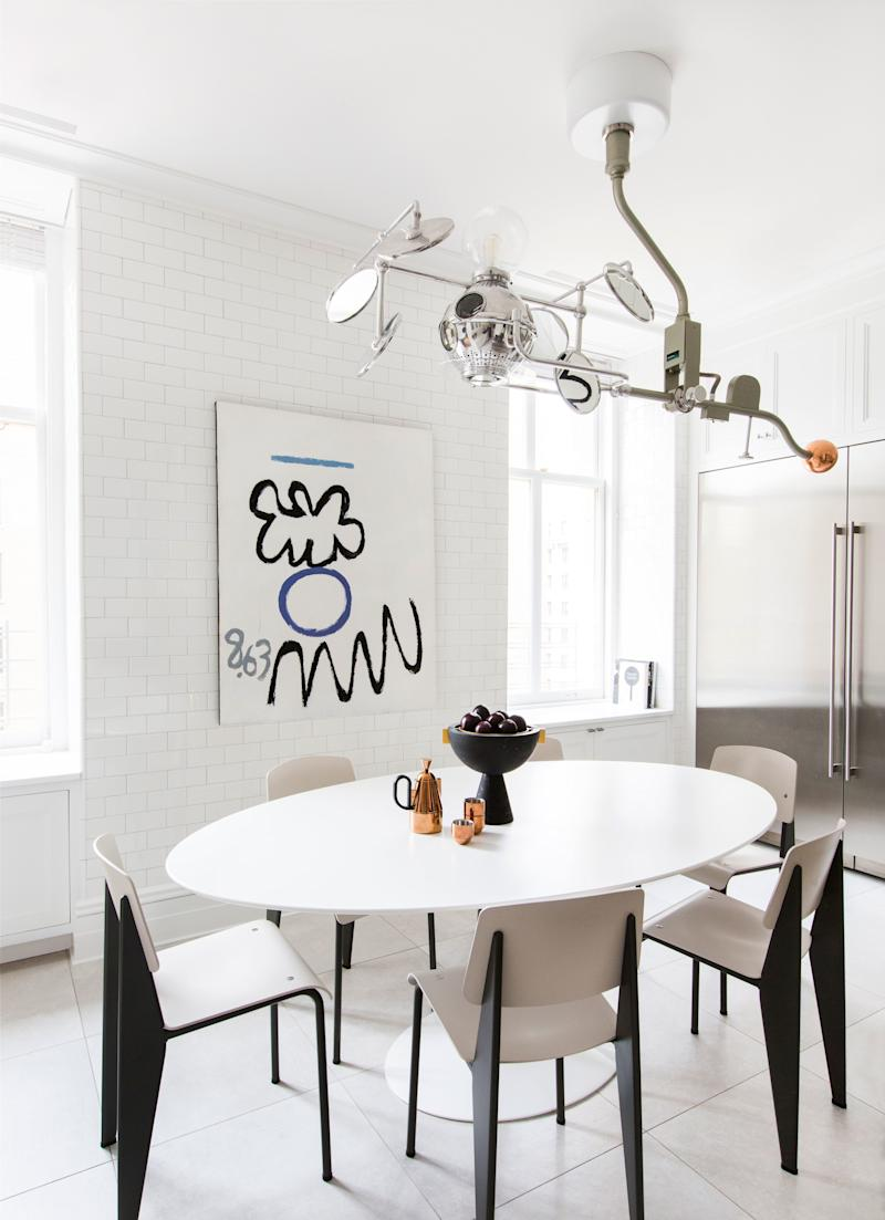 """The kitchen, which was covered in white subway tiles in a nod to New York City, features a distinctive light pendant made from an old surgical light fused with Sofie Refer's """"Mega Bulb"""" glass fixture for andTrandition. Jean Prouvé's famous chairs surround Eero Saarinen's equally iconic pedestal table. The abstract artwork is a painting by Raymond Hendler called The General."""