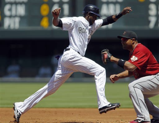 Colorado Rockies' baserunner Dexter Fowler, left, jumps back to first base as Houston Astros first baseman Carols Lee fields a pickoff throw in the first inning of game one of a day/night doubleheader in Denver on Monday, May 28, 2012. (AP Photo/David Zalubowski)