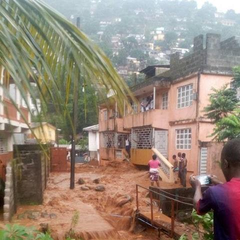 Villagers look on in this image that reportedly shows the aftermath of the Sierra Leone mudslide - Credit: Society for Climate Change Communication Sierra Leone