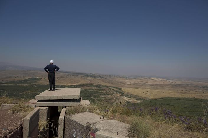 In this photo taken, Tuesday, July 24, 2012, a Druse man looks toward the nearby Syrian village of Jebata al-Khashab from an Israeli army post near the village of Bukata in the Golan Heights. Horrified by the carnage that's reached their doorstep, more and more Druse Arabs in the Golan Heights are turning against a Syrian regime to which they remained at least outwardly loyal throughout decades of Israeli occupation. (AP Photo/Tsafrir Abayov)