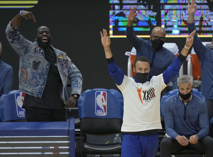 Golden State Warriors' Draymond Green, left, and Stephen Curry, front right, celebrate after Jordan Poole scored a three-point basket against the New Orleans Pelicans during the first half of an NBA basketball game on Friday, May 14, 2021, in San Francisco. (AP Photo/Tony Avelar)