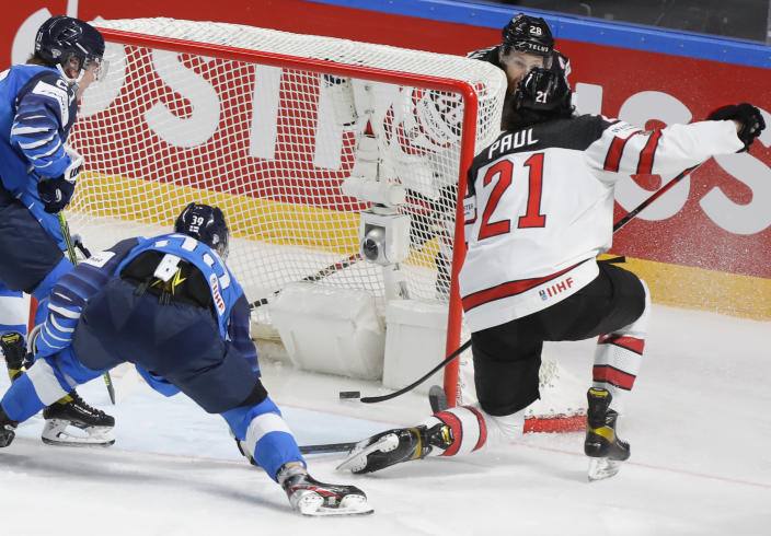 Canada's Nick Paul, right, scores to win the Ice Hockey World Championship final match between Finland and Canada at the Arena in Riga, Latvia, Sunday, June 6, 2021. (AP Photo/Sergei Grits)