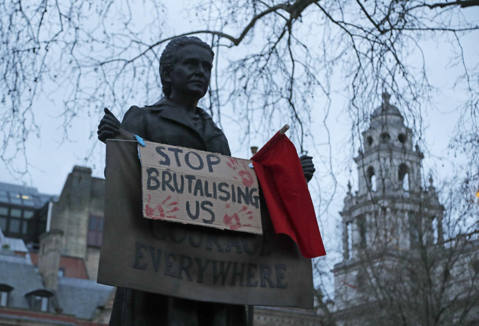 A placard hangs from a statue of suffragist Millicent Garrett Fawcett as demonstrators gather during a protest in Parliament Square in London, Sunday, March 14, 2021. London's Metropolitan Police force was under heavy pressure Sunday to explain its actions during a vigil for Sarah Everard whom one of the force's own officers is accused of murdering. (AP Photo/Frank Augstein)