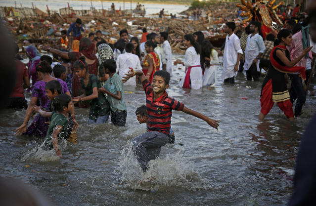 <p>An Indian Hindu boy dances in the River Yamuna during immersion of idols of goddess Durga on the final day of Durga Puja festival in New Delhi, India, Saturday, Sept. 30, 2017. The immersion of idols marks the end of the festival that commemorates the slaying of a demon king by lion-riding, 10-armed goddess Durga, marking the triumph of good over evil. (Photo: Altaf Qadri/AP) </p>