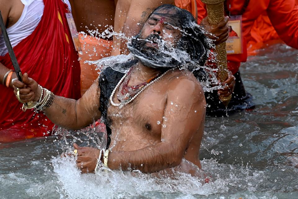 A Naga Sadhu (Hindu holy man) takes a holy dip in the waters of the Ganges River on the day of Shahi Snan (royal bath) during the ongoing religious Kumbh Mela festival, in Haridwar on April 12, 2021. (Photo by Money SHARMA / AFP) (Photo by MONEY SHARMA/AFP via Getty Images)