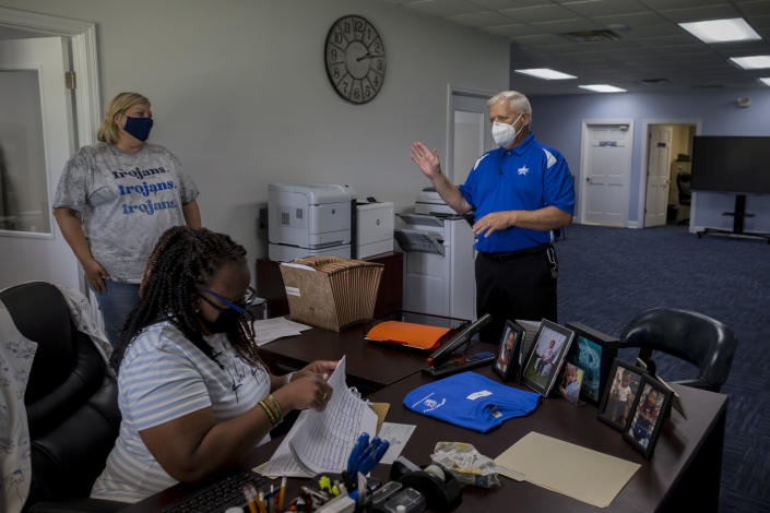 Johnson County Board of Education Superintendent Eddie Morris, right, speaks with his staff outside his office, Friday, Aug., 20, 2021, in Wrightville, Ga. A few weeks into the new school year, growing numbers of U.S. districts have halted in-person learning or switched to hybrid models because of rapidly mounting coronavirus infections. With 40% of students in quarantine or isolation, the Johnson County district shifted last week to online instruction until Sept. 13. (AP Photo/Stephen B. Morton)
