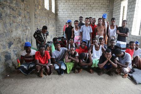 Somali refugees who survived an attack on a boat off Yemen's coast in the Red Sea pose for a group photo as they wait at a detention center in the Houthi-held port of Hodeidah, Yemen