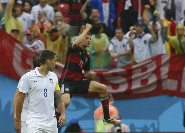 Germany's Thomas Mueller (R) celebrates his goal as Clint Dempsey of the U.S. walks in front of him during their 2014 World Cup Group G soccer match at the Pernambuco arena in Recife June 26, 2014. REUTERS/Yves Herman (BRAZIL - Tags: SOCCER SPORT WORLD CUP)