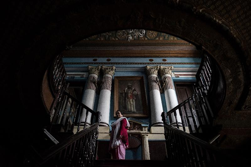 Chief librarian Janaki Karmacharya, 58, goes up the stairs of the Kaiser Library in Kathmandu on May 7, 2015 (AFP Photo/Philippe Lopez)