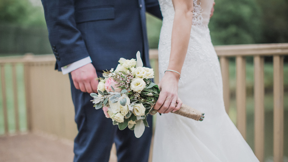 Bride and groom on wedding day, focus on bouquet.